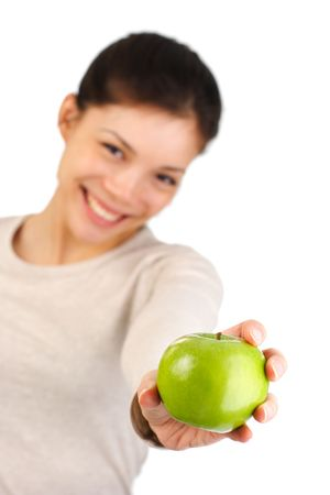 Have an apple! Beautiful smiling young woman giving a green apple. Isolated on white.  photo