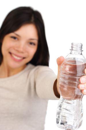 sediento: Hermosa mujer con una botella de agua. Botella en el punto de mira, el modelo fuera de foco. Aislado en blanco. Foto de archivo