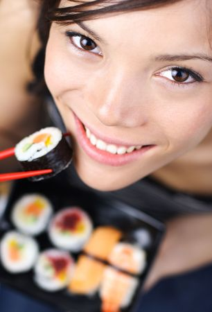 Beautiful young woman eating sushi. Shallow depth of field, focus is on the eyes.