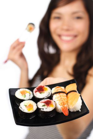 Smiling young woman presenting a plate of sushi. Shallow depth of field, focus on sushi. photo