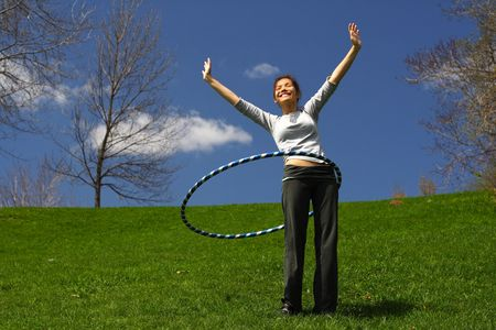 hoops: Beautiful young woman doing plastic hoop outdoors on a sunny spring day. Stock Photo