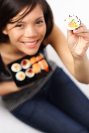 Cute sushi woman showing a salmon maki sushi. photo