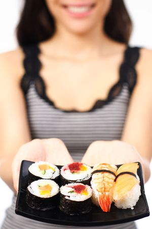 Woman presenting a plate of sushi. Shallow depth of field with focus on the sushi. photo