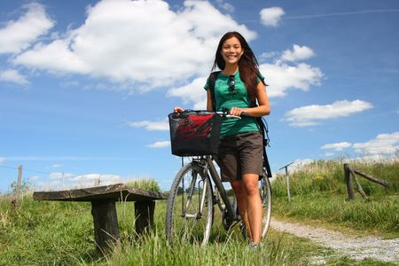 Beautiful young woman walking with her bike, in the countryside of Jutland, Denmark. photo