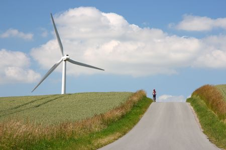 Woman biking among windmills and wheat fields in the countryside of Jutland, Denmark.  photo