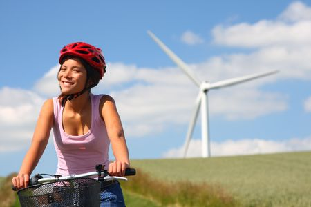 Woman relaxing and enjoying the sun on a bike trip in the countryside of Jutland, Denmark Windmill in the background. photo