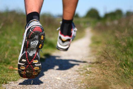 szlak: Trail uruchomiony. Freeze działania z bliska, buty do biegania w akcji. Płytka głębia ostrości, koncentrują się na lewo buta. Zdjęcie Seryjne