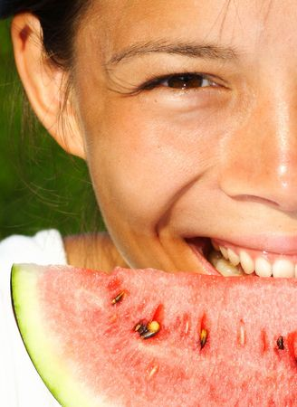 Beautiful woman smiling while eating watermelon outdoors on a hot summerday Stock Photo - 5145056