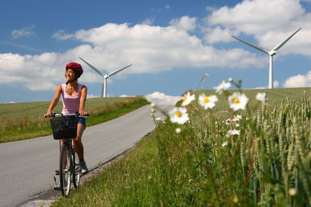 Woman relaxing and enjoying the sun on a bike trip in the countryside of Jutland, Denmark Windmill in the background.