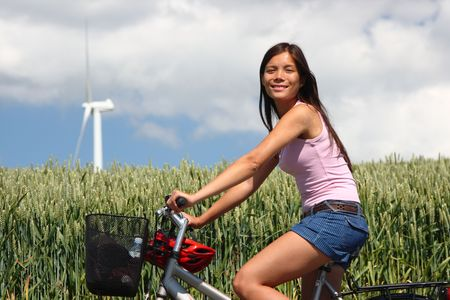 denmark: Young woman relaxing and enjoying the sun on a bike trip in the countryside of Jutland, Denmark. Wind turbine on a wheat field in the background.