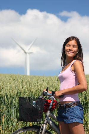 Young woman relaxing and enjoying the sun on a bike trip in the countryside of Jutland, Denmark. Wind turbine on a wheat field in the background. Stock Photo - 5145057