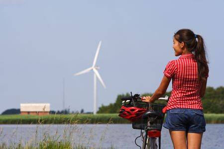 Woman relaxing and enjoying the sun on a bike trip in the countryside of Jutland, Denmark Windmill in the background. Stock Photo - 5174600