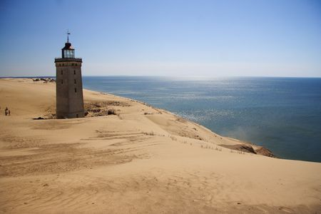 Lighthouse in the sand dunes of Rubjerg Knude in Denmark photo