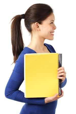 Smiling female university student showing blank yellow notebook. Isolated on white background photo