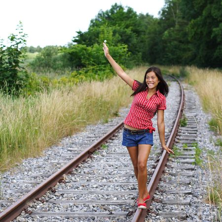 Beautiful young mixed race woman balancing on railway tracks  rails. From Denmark. photo