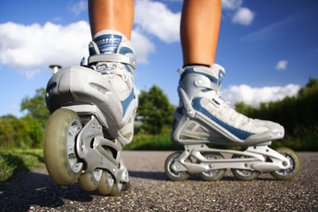 inline skates: Inline skates in action closeup. Shallow depth of field, focus on left skate.