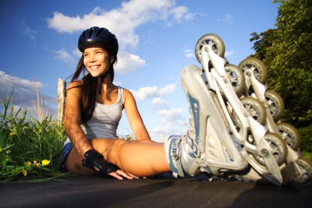 roller skates: Woman on rollerblades taking a rest on a sunny day.