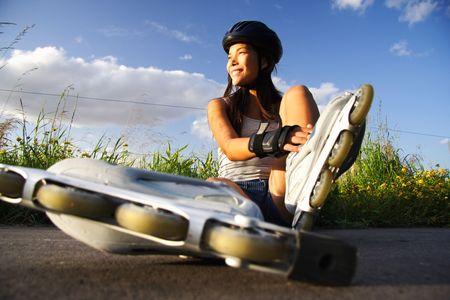 Asian woman on inline rollerblades enjoying a break.