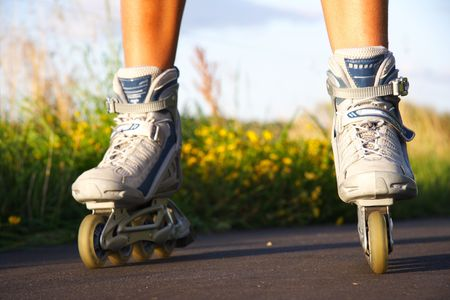 inline skates: Rollerblades in action closeup on a sunny summer evening.