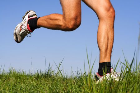 cross leg: Iconic running image. Freeze action closeup of running shoes and legs in action.  Stock Photo