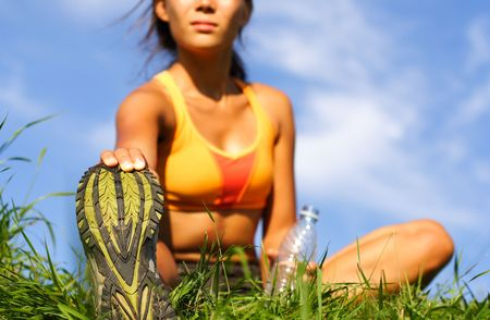 Woman stretching out during outdoor excercise in summer. Sitting in the grass. photo
