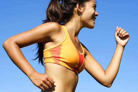 closeup of sporty woman runner in profile on a hot summer day. Stock Photo