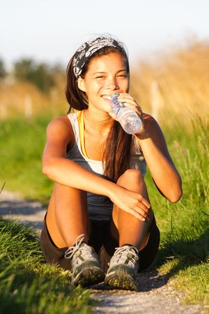 Sporty mixed asian  caucasian drinking water after running outdoor in summer. photo