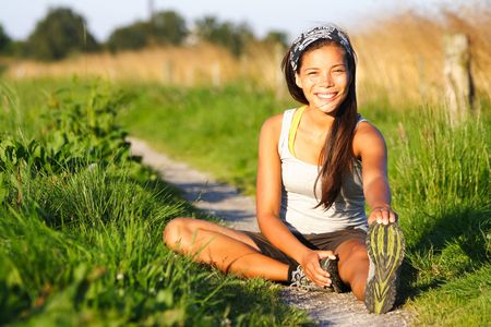 Woman stretching out during outdoor excercise a summer night. Sitting in the grass. Stock Photo