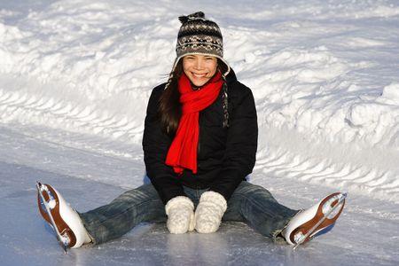 patinando: Patinaje sobre hielo. Joven mujer sentada en el hielo, mientras que fuera de patinaje en un soleado d�a de invierno en la ciudad de Quebec.