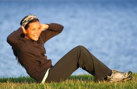 asian abs: Woman doing situps  exercise outdoors on grass with the ocean in the background