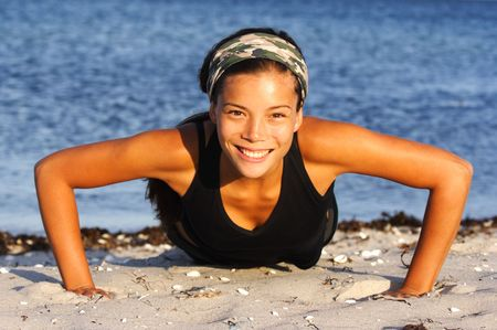 ups: Attractive woman doing push-ups on the beach. Stock Photo