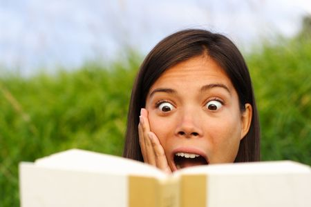 excited people: young beautiful woman surprised by the story she is reading in her book.