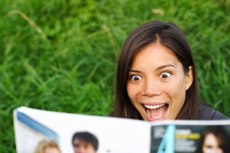 magazine reading: Excited woman surprised by gossip she is reading in magazine.