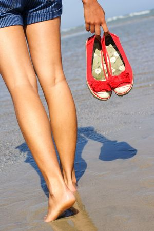 girl in shorts: woman walking on the beach holding her shoes