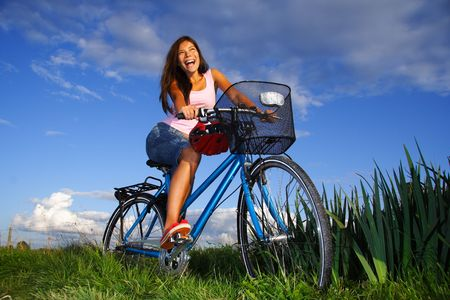 Woman biking under deep blue sky in the countryside of Jutland, Denmark during summer. Beautiful happy woman. photo