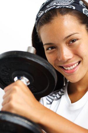 Attractive woman lifting weights and smiling at the camera. Closeup. photo