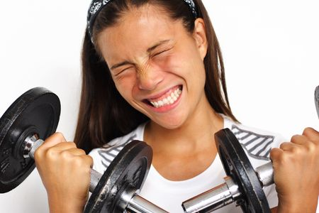 working model: Attractive woman pushing herself while lifting weights. Closeup. Stock Photo