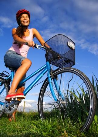 actividades recreativas: La mujer en bicicleta bajo el cielo azul profundo en el campo de Jutlandia, en Dinamarca durante el verano. Hermosa mujer feliz.