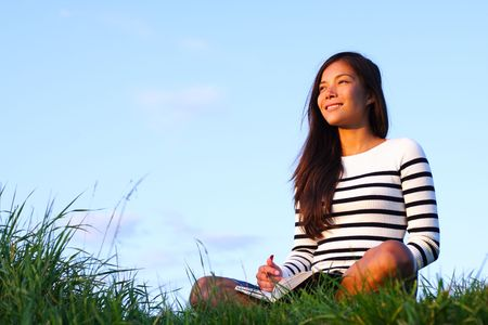 blue sky thinking: Woman studying outside in evening light with copy space. Beautiful mixed asian  caucasian woman. Stock Photo