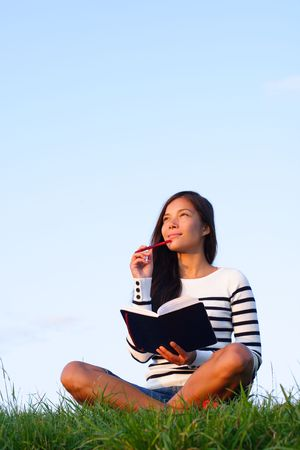 blue sky thinking: Woman thinking hard studying outside in evening light with a lot of copy space. Beautiful mixed asian  caucasian woman.