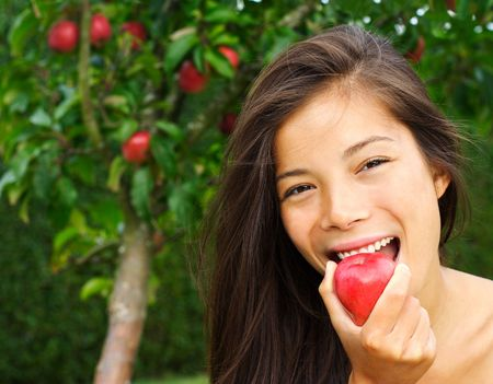 Apple woman. Very beautiful ethnic model eating red apple in the park. Stock Photo - 5439819