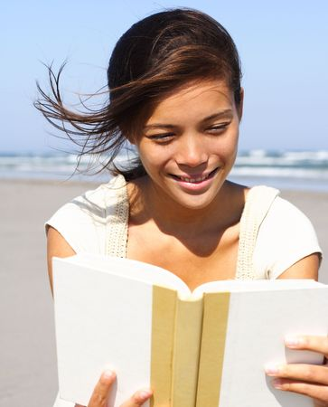 Candid image of a woman reading a book on the beach photo