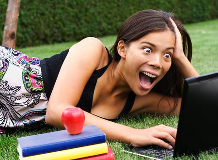 Student with laptop surprised while chatting  checking email  reading gossip news in the park. Beautiful mixed race caucasian  asian model.