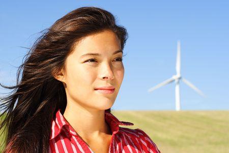 Wind turbine. Beautiful woman by wind turbine in Denmark.