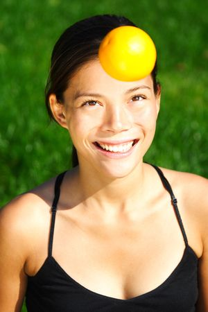 Orange and health concept -   cute picture of young woman throwing an orange in the air. T photo