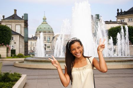 Young woman doing peace sign while visiting the city of Copenhagen, Denmark during summer. photo