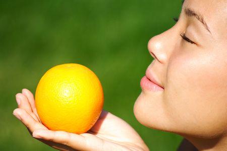 Pretty woman disfrutar el olor de una naranja durante el verano.