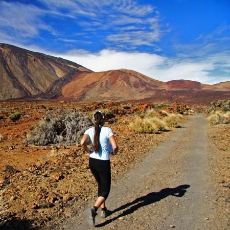 Runner, Woman running on dirt road in amazing volcano landscape on Tenerife. photo