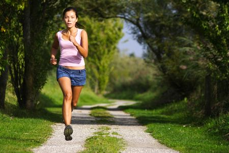 jogging track: Running. Woman running at great speed. Freeze action image on beautiful forest path. Beautiful model. Stock Photo