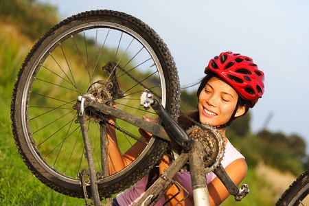 Bike repair. Woman repairing mountain bike. Beautiful smiling woman. photo